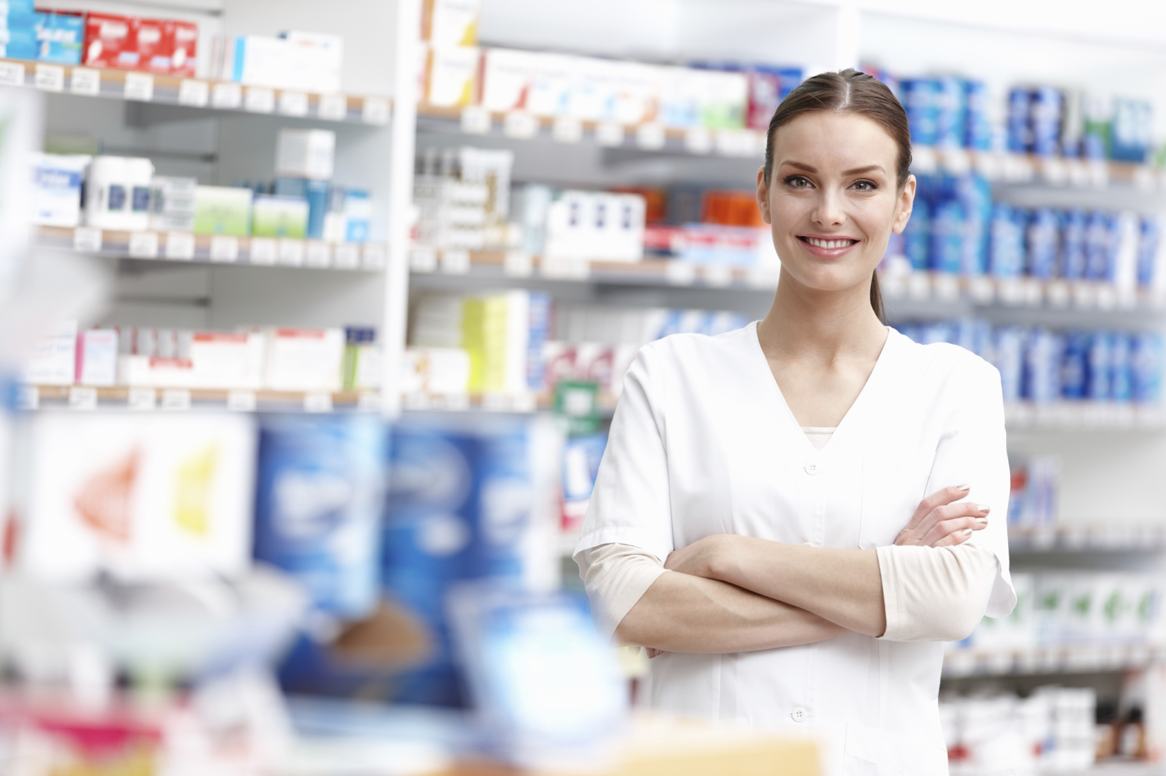 Portrait of young pharmacist smiling with hands folded at medical store
